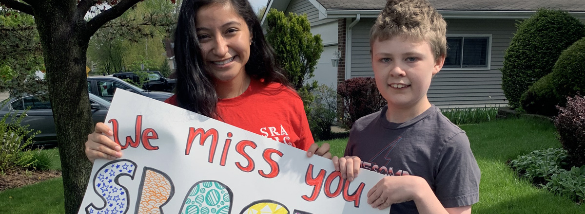Youth Holding a 'We miss you' sign